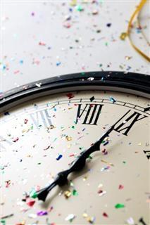 Clock showing midnight, with coloured confetti