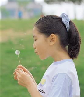 Girl blowing a dandelion clock